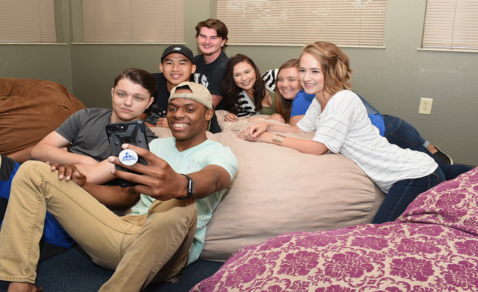 Student group selfie in residence hall lounge