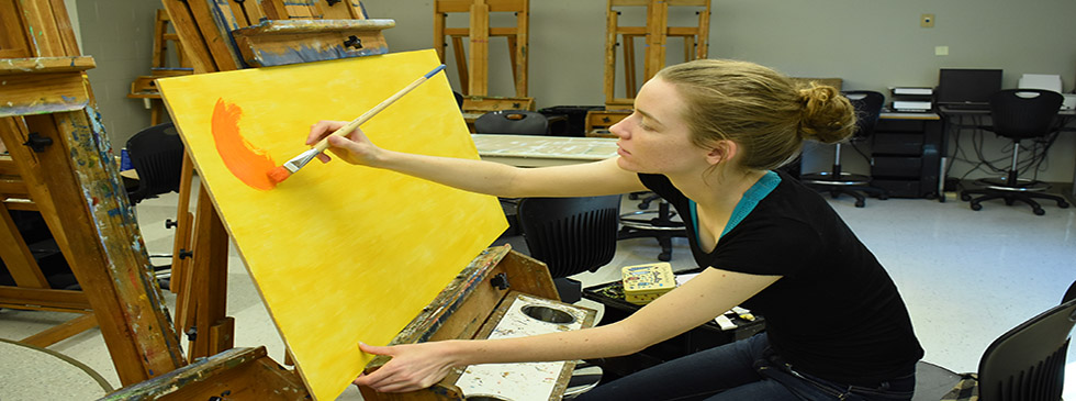 art student painting in lab on oversized easel.