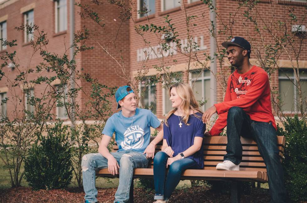 Students on park bench outside resdience halls