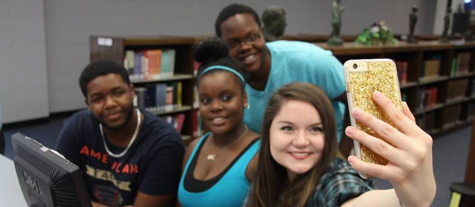 Students taking selfie in library at study table