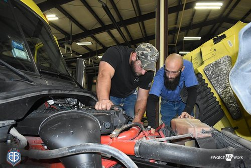 Instructor and student looking above diesel engine.
