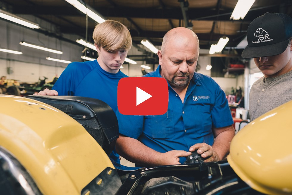 Instructor showing two students how to repair All Terrain Vehicle